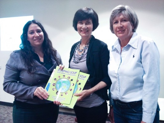 Gladstone Women's Intercultural Network coordinator Natalia Muszcat checks out 'Slurping Soup' with Kathryn Tonges and her sister Julie Charles a WIN volunteer.